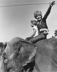 Leta and her son ride an elephant - Click to see larger version